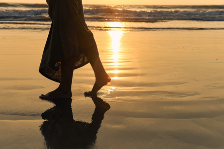 Romantic young girl walks on the beach barefoot in the water. Woman stroll barefoot in the sea at sunset. Beautiful female legs in the ocean. Silhouette of a female body in a dress on sea background.