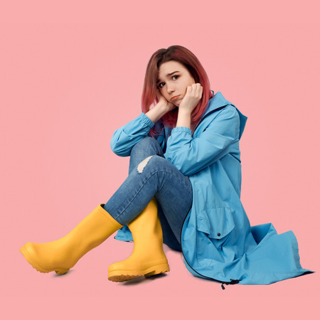 a young beautiful girl in a blue coat and yellow rubber boots sits with a sad and sad expression in her eyes. She is depressed by the spoiled rainy weather.