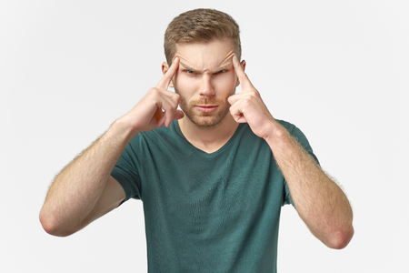 Upset man looks at camera, keeps hands on temples, raises eyebrows model against white wall in studio.