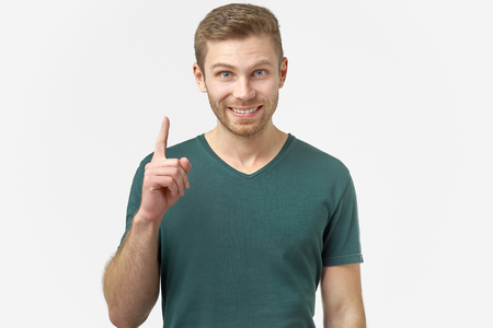 Stunned male points with fore finger upwards, he gets a good idea or good news about a successfully passed exam. Excited cheerful man remembers something nice, isolated on white background.