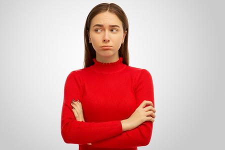 Foto der jungen Frau empfindet Hass und will nicht reden. Porträt eines Mädchens mit dunklem Haar, verschränkten Armen, Stirnrunzeln, enttäuscht und traurig. Getrenntes Studioporträt auf weißem Hintergrund.
