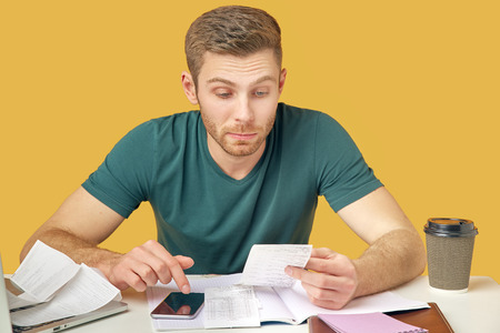 The guy in the green t-shirt puzzled studying checks and bills, analyzes the costs of counting on a calculator sitting at the table. The concept of the family budget and financial problems.
