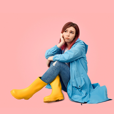 Square shot of young beautiful girl wearing spring raincoat protected from the rain and tall yellow rubber boots sits with sad expression in her eyes. She is depressed by spoiled rainy weather.