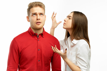 Studio portrait of a young colleagues. The concept of failure. Angry bearded man listens to reproaches of woman. Female screams with negative emotions on colleague, shout in annoyance.