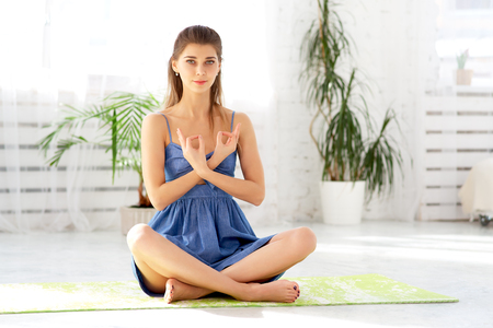 Beautiful calm female meditating in easy pose at home sitting on mat, holding hands, yogic gesture, practicing yoga in cozy living room, breathing air exercises, no stress, spiritual growth.