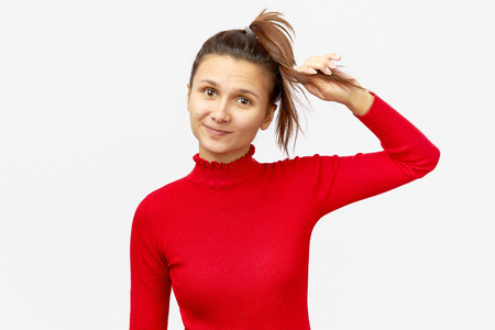 Adorable girl wears red sweater, makes pony tail. Smiling delightful woman has attractive appearance going to have walk outdoor. Stock Photo