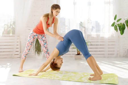 Group of young people practising yoga with senior trainer helping to keep yoga poses in the white studio. Woman helping her friend to open shoulders and chest doing yoga asana.