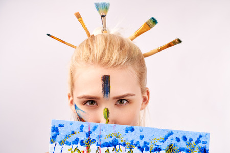 Close up shot of female has artistic makeup in the form of strokes acrylic paint. Creative girl looks out of picture, you can see only eyes. Stylish Bob hairstyle with stuck brushes in blond hair.