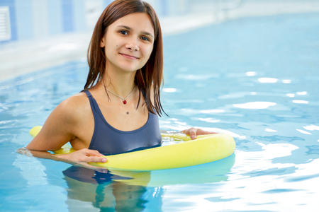 Happy smiling sportive woman doing exercise in a swimming pool. Exercising in swimming pool with the help of a aqua tube. Young healthy female doing aerobics.