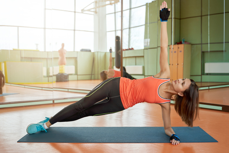 Sports woman standing in the pose of the bar on the elbow, raises hand up, stretches whole body to the ceiling.