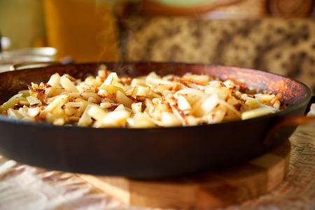Gebackene knusprige goldene frittierte Pommes frites heiße Kartoffeln braten und essfertig. Bratkartoffeln in der alten gusseisernen Pfanne. Wirklich lecker. Standard-Bild