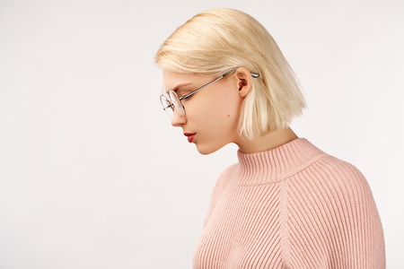 Profile of serious female with healthy pure skin, wears round glasses, has contemplative expression, isolated over white studio wall with copy space. Banque d'images