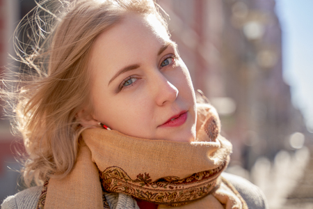 Portrait of serious girl in the autumn on background of City. Fashionable women in scarf and red lipstick looking at camera. Фото со стока
