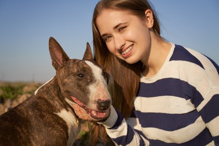 A beautiful woman wearing a striped jumper hugging a bull Terrier dog on a field background. A happy girl with a snow-white smile laughs and enjoys a walk in the open air.