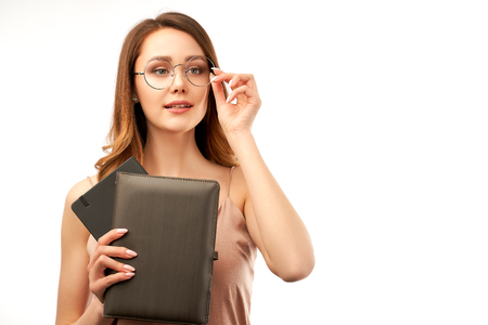 a pretty young brunette girl holds a notebook in her hands and holds her glasses with hand, trying to see the inscriptions.
