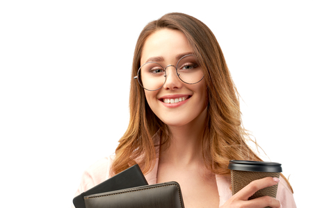 long-haired cute smiling brunette business lady holding a folder with documents and a Cup of coffee or tea. she is energetic and ready for a productive working day.