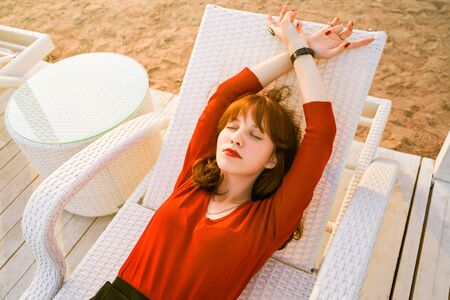 Top view of beautiful red-haired girl. Young woman lying on sun lounger, sunbathing, closes pleasure of eyes, enjoys warm summer evening. Portrait of chic stylish lady resting after long day's work. 写真素材 - 132839137
