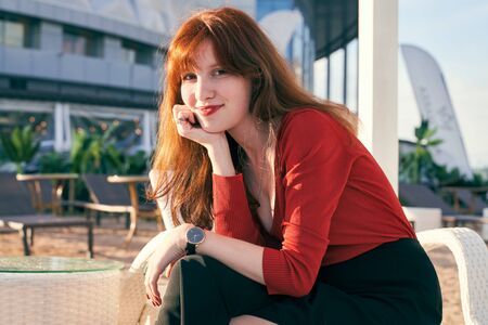 An attractive young girl with long curly redhead hair has bright red lipstick and freckles, wearing jumper and skirt, sitting on white chaise longue on terrace cafe by river. Sunny evening in summer. Stock Photo