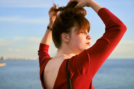 Ginger haired woman ties her long hair into knot. Photo of the girl back. The plunging neckline on red dress. The lady enjoys evening sea breeze standing on bridge.