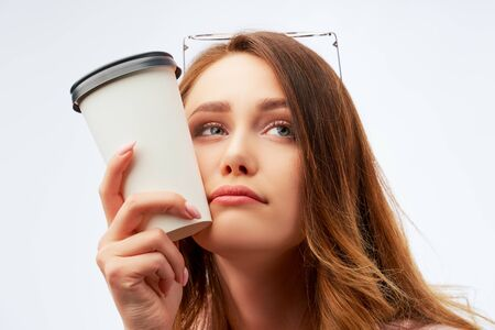 Large portrait of pretty pensive stylish student girl with dark wavy loose hair, having break, holding coffee cup near her face, looking aside with dreamy expression, recalling some pleasant moments. Фото со стока
