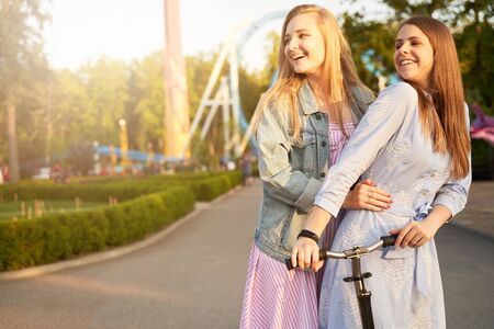 Two beautiful young long haired women, best friends, wearing pretty summer dresses, having fun in amusement park in warm summer day, looking happily, satisfied with meeting and time together. 写真素材 - 132839349