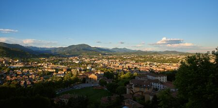 Panorama view on Bergamo city with Alps mountains and blue cloudy sky in far background. Roofs of churches, houses and old buildings and architecture from top view point.