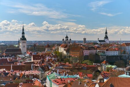 Picturesque view over Tallinn historic center with old buildings with colorful roofs and chimneys, fortress towers and walls made of brick, cozy narrow streets, cathedral bell towers on a spring day.