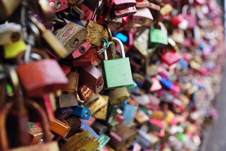 Tens colorful metal pad locks, love locks, with people names engraved, symbolizing eternal unbreakable love, relationship between two loving people. Famous city landmark of Cologne, Germany. Imagens
