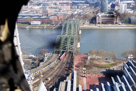 Panoramic aerial view over Cologne historic city center, downtown, with colorful historical buildings, gothic cathedral towers, the Rhine river and modern bridge against beautiful sunny spring sky.