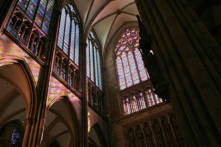 Interior Cologne Cathedral, Germany. Inside view of a huge elegant colorful stained glass window with pastoral and religious scenes and ornate floral metal decor.
