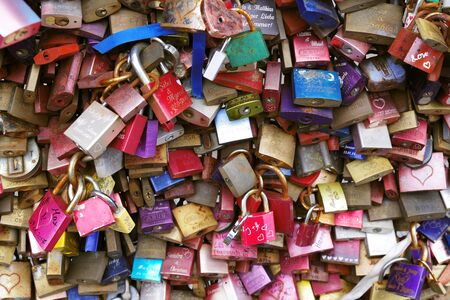 Tens colorful metal pad locks, love locks, with people names engraved, symbolizing eternal unbreakable love, relationship between two loving people. Famous city landmark of Cologne, Germany. Stock Photo