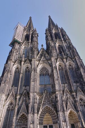 View over amazing, gothic, richly decorated facade of the Cologne Cathedral (Kolner Dom) against clear blue sky. World heritage and famous landmark of the city of Cologne, Germany.