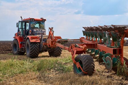 The concept of agriculture and agricultural machinery. Tractor plows field, cultivators soil for sowing grain. Powerful red auto works in field. Tractor for tillage and field preparation for planting Zdjęcie Seryjne