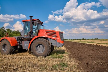 The concept of agriculture and agricultural machinery. Tractor plows field, cultivators soil for sowing grain. Powerful red auto works in field. Tractor for tillage and field preparation for planting