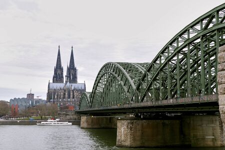 Panoramic view over Cologne historic city center, downtown, with colorful historical buildings, gothic cathedral towers, the Rhine river and modern bridge against dull spring sky. Imagens