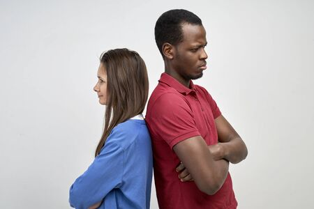 A young African and European couple stand with their backs against the white wall. Two people got into a fight and dont compromise.