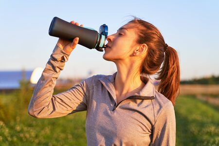 A young girl after workout drinking water Imagens