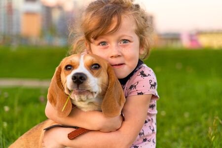 Freckled girl hugs joyfully her best friend. Foto de archivo