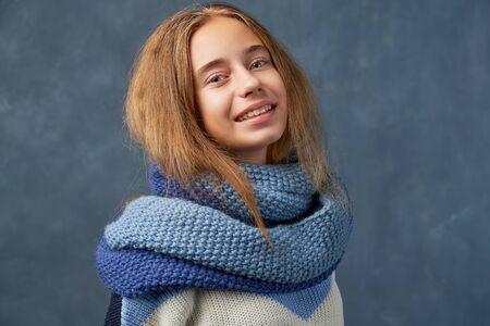 Teenage girl blonde in warm sweater isolated wall