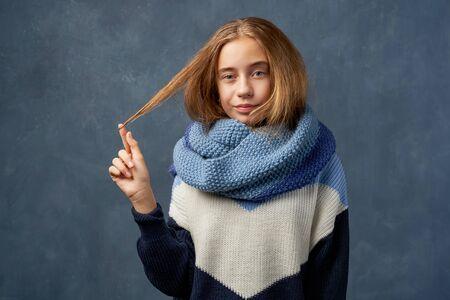 Teenage girl blonde in warm sweater isolated wall Banco de Imagens