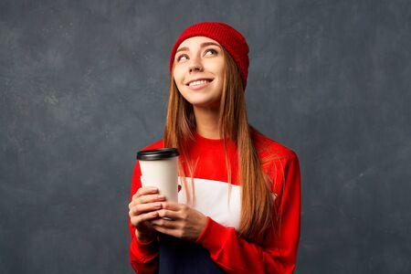 girl holds mug of coffee isolated on textured wall Фото со стока