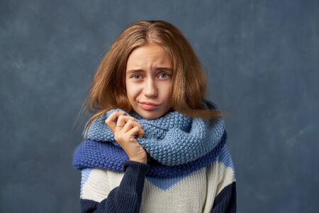 Teenage girl blonde in warm sweater isolated wall Banque d'images - 131689666