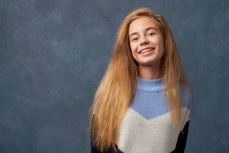 Teenage girl blonde in warm sweater isolated wall 版權商用圖片
