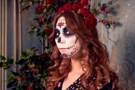 Photo of young woman has face arfully painted to resemble skulls. People preparing for popular carnival, dressed in costume, applied makeup in shape of skull. Day of dead holiday in Mexico. Halloween. Stock fotó - 131596742