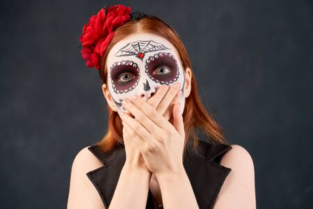 Portrait of scared woman, covering her mouth with both palms to prevent screaming sound, after seeing something bad. People preparing for popular carnival dressed in costume applied makeup shape skull 免版税图像