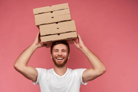 Courier holds many pizza boxes isolated on wall