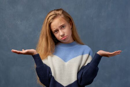 Teenage girl blonde in warm sweater isolated wall Stock fotó