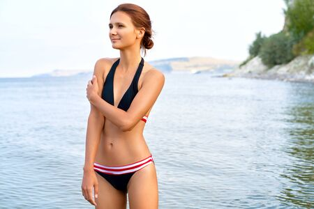 Happy slender woman stands in water against sea