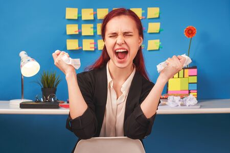 Woman holds lumps of paper hands yells irritably