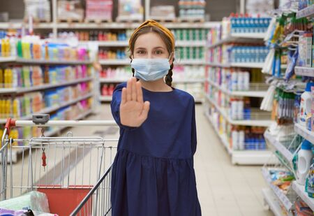 Girl in medical mask reaches hand shows stop sign